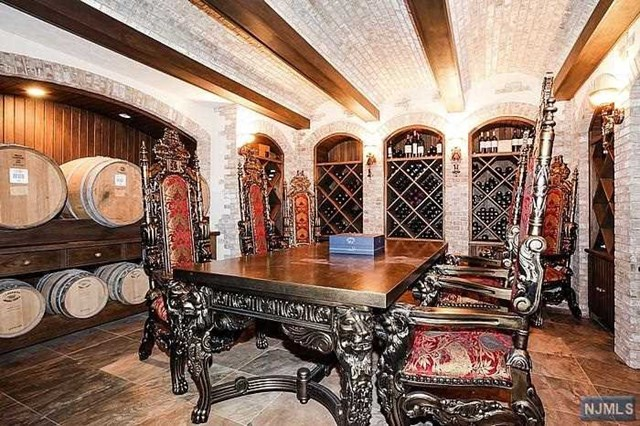 The wine room in this Franklin Lakes, NJ property listed by William Boswell has ornate carved wooden furniture and enough room for both bottle and cask storage is truly fit for a king.