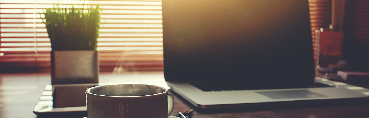 Electronic business distance work via internet focus on the cup of american coffee