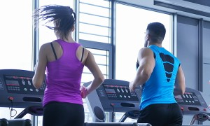 group of young people running on treadmills in modern sport  gym