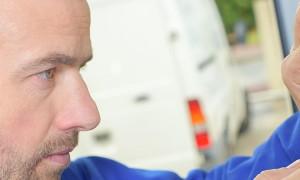 Man inspecting a damaged fusebox