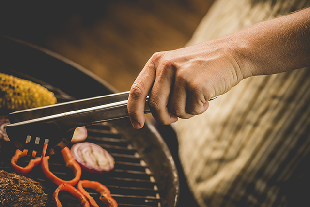Still of a hand with barbecue tongs moving food on the barbecue