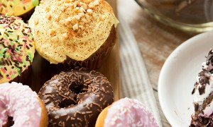 junk food, culinary, baking and eating concept - close up of glazed donuts, cakes and chocolate swee