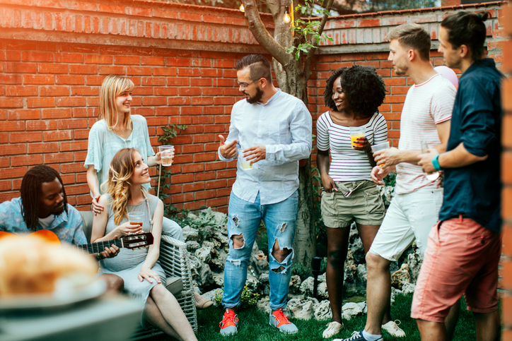 Happy young people at the party in the backyard talking and smiling. One young man playing guitar. They are enjoy spending time together.