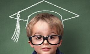 Child holding stack of books with mortar board chalk drawing on blackboard concept for university ed
