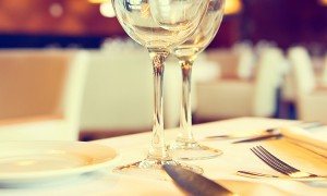 Served dinner table in a restaurant. Restaurant interior. Cozy restaurant table setting. Defocused b