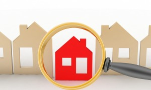 Magnifying glass selects or inspects a home in a row of houses. Concept of search of house for resid