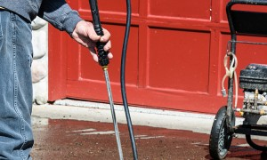 Man Cleaning Driveway with Pressure Washer