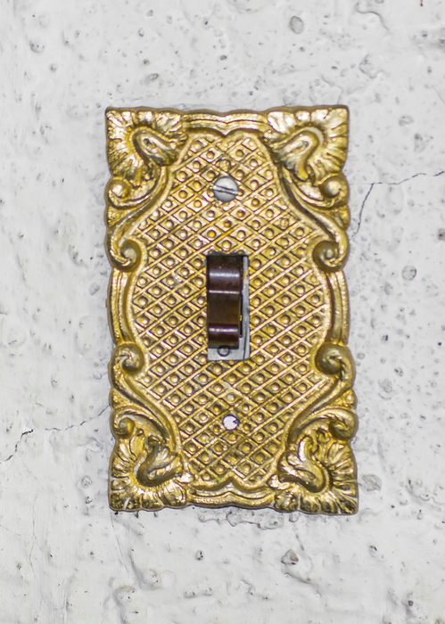 Old style ornate in golden tones lightswitch in white wall