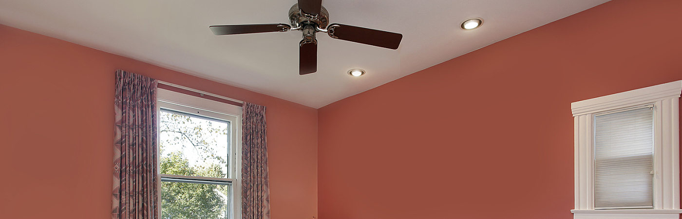 Master bedroom with peach colored walls and ceiling fan