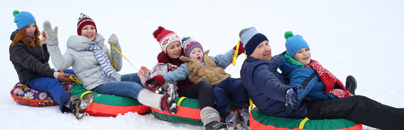 Six happy people sits on four snow tubes in snow winter day