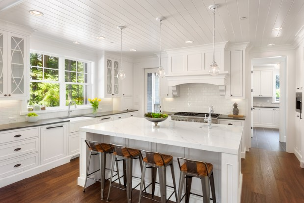 White Kitchen Interior with Island, Sink, Cabinets, and Hardwood Floors in New Luxury Home with Lights On