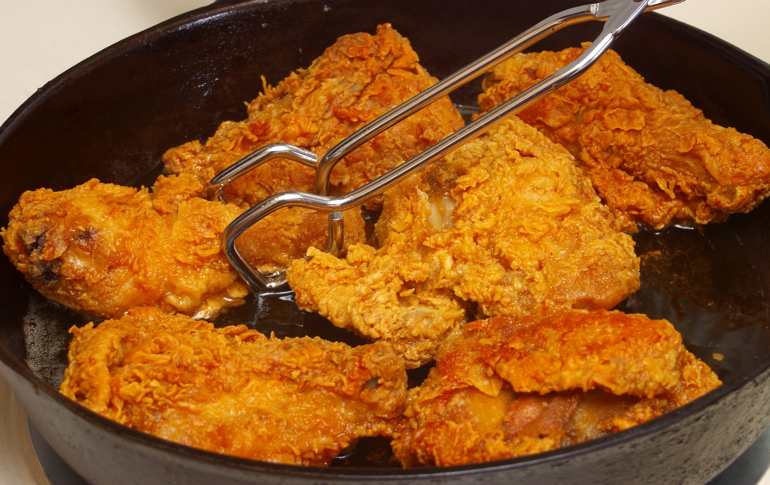Chicken cooking in a cast-iron frying pan
