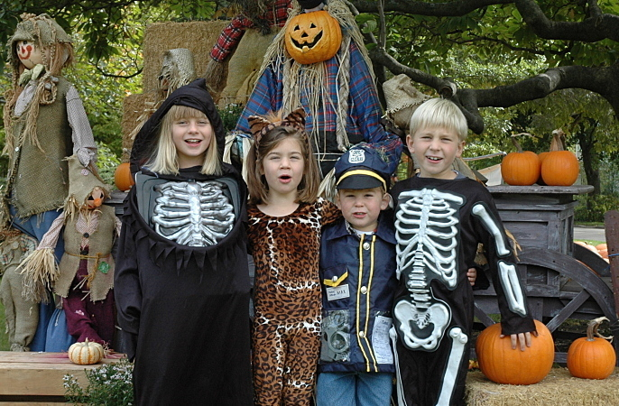 Kids on Halloween standing in front of a scarecrow